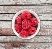 Raspberries in a white ceramic bowl. Royalty Free Stock Photo