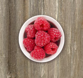 Raspberries in a white ceramic bowl. Stock Photos