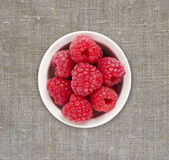 Raspberries in a white ceramic bowl. Ripe and tasty raspberries on a linen tablecloth. Top view Royalty Free Stock Image