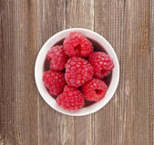 Raspberries in a white ceramic bowl. Ripe and tasty raspberries  on a wooden background. Top view Royalty Free Stock Image