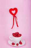Raspberries in white cup and heart. On pink background Stock Images