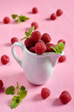 Raspberries in a white jug with mint. Leaves royalty free stock photos