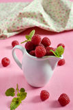 Raspberries in a white jug with mint. Leaves stock photo