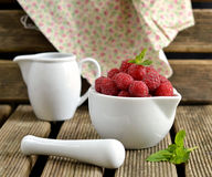 Raspberries in a white jug with mint. Raspberries in a white mortar jug with a pestle royalty free stock image