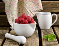 Raspberries in a white jug with mint. Raspberries in a white mortar jug with a pestle stock photo