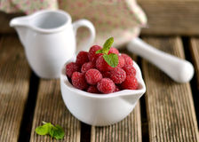 Raspberries in a white mortar jug with a pestle. Ripe raspberries in a white mortar jug with a pestle stock photography