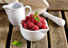 Raspberries in a white mortar jug with a pestle. Ripe raspberries in a white mortar jug with a pestle stock image