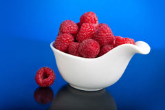 Raspberries in a white pialat. On blue background Royalty Free Stock Photography