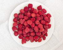 Raspberries on a white plate. Raspberries lying in a form of triangle on a white plate with background made of linen tablecloth Stock Photo