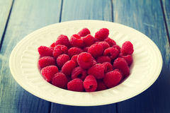 Raspberries on white plate on blue background. Raspberries on white plate on blue wooden background Stock Images