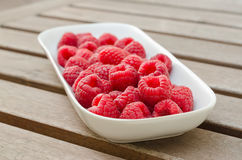 Raspberries on a white plate. Fresh organic raspeberry on a white plate on a wooden table Royalty Free Stock Image