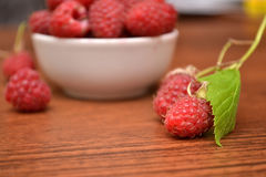 Raspberries in white plate on a wooden table. Raspberry branch. Natural texture. Royalty Free Stock Photography