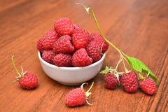 Raspberries in white plate on a wooden table, raspberry branch. Raspberrie on the table. Natural texture. Stock Image
