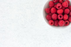 Raspberries in White Porcelain Bowl. Raspberries in a white porcelain bowl isolated on white marble background with lots of copy space Royalty Free Stock Photography