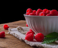 Raspberries in white porcelain plate. Side view on handful of ripe and fresh raspberries in white porcelain cup against black background Stock Photo