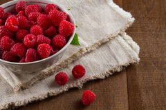 Raspberries in white porcelain plate. Side view on handful of ripe and fresh raspberries in white porcelain cup against black background Royalty Free Stock Photo
