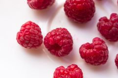 Raspberries on a white saucer close up. Big fresh juicy raspberries on a white saucer close up, selected focus Stock Photo