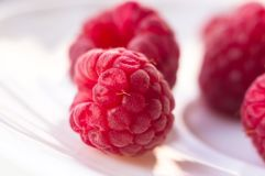 Raspberries on a white saucer close up. Big fresh juicy raspberries on a white saucer close up, selected focus Royalty Free Stock Photo