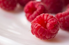 Raspberries on a white saucer close up. Big fresh juicy raspberries on a white saucer close up, selected focus Royalty Free Stock Images