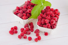 Raspberries on a white table. Fresh raspberries in cardboard boxes on a white wooden table Royalty Free Stock Image