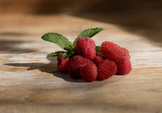 Raspberries on wood with mint. Fresh Raspberries with mint leaves on wooden table Stock Photo