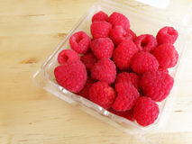 Raspberries on wood table. Fresh red raspberries in a plastic container tray, placed on wooden table in bright sunlight.  Still life photo with simple Royalty Free Stock Photo