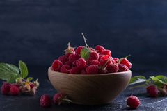 Raspberries in wooden bowl on black background. Fresh ripe sweet berries, healthy food. Raspberries in wooden bowl on black background. Fresh ripe sweet berries Stock Photo
