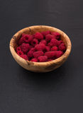 Raspberries in a wooden bowl on black slate stone background. Fresh raspberries in a wooden bowl on black slate stone background Stock Photo