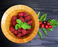 Raspberries. In a wooden bowl on black wooden background Stock Photography