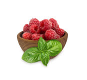 Raspberries in a wooden bowl isolated on white background. Raspberry with basil close-up. Vegetarian or healthy eating. Juicy and delicious raspberries Royalty Free Stock Photos