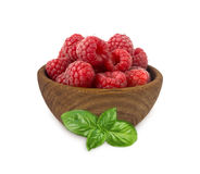 Raspberries in a wooden bowl isolated on white background. Raspberry with basil close-up. Vegetarian or healthy eating. Juicy and delicious raspberries Stock Images