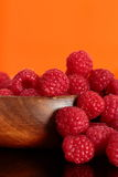 Raspberries in a wooden bowl. Reflected Stock Images