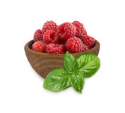 Raspberries in a wooden bowl  on white background. Raspberry with basil close-up. Vegetarian or healthy eating. Juicy and delicious raspberries Stock Photo