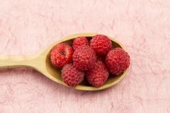 Raspberries in wooden spoon on a pink napkin. Healthy vegetarian food. Diet Royalty Free Stock Photography