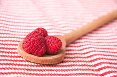 Raspberries in a wooden spoon on striped. Pink raspberries in a wooden spoon on a red-white striped background Royalty Free Stock Photography