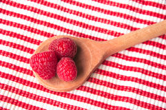 Raspberries in a wooden spoon on striped. Pink raspberries in a wooden spoon on a red-white striped background from above Royalty Free Stock Photo