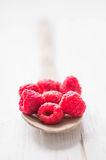 Raspberries in wooden spoon on white background Stock Photo