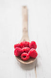 Raspberries in wooden spoon on white background Stock Images