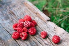 Raspberries on a wooden surface. Berries on a wooden surface. Heap of sweet raspberries, top view close up Royalty Free Stock Images