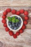 Vertical picture of heart shaped raspberries, in the middle a white bowl of blueberries royalty free stock images