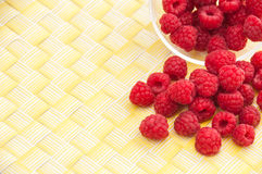 Raspberries on a yellow background. A glass bowl of raspberries in a yellow background Royalty Free Stock Photography