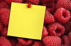 Raspberries and yellow note. Beautiful ripe juicy raspberries and yellow paper note Stock Photos
