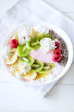 Raspberry and banana smoothie bowl with kiwi slices, shredded co. Conut and chia seeds. Healthy food concept Stock Image