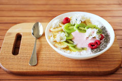 Raspberry and banana smoothie bowl with kiwi slices, shredded co Stock Image