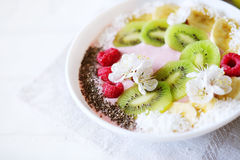 Raspberry and banana smoothie bowl with kiwi slices, shredded co Stock Photography