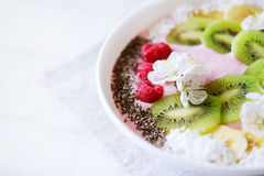 Raspberry and banana smoothie bowl with kiwi slices, shredded co Royalty Free Stock Image