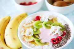 Raspberry and banana smoothie bowl with kiwi slices, shredded co Royalty Free Stock Images