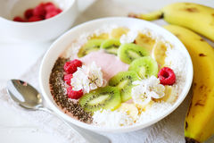 Raspberry and banana smoothie bowl with kiwi slices, shredded co Royalty Free Stock Photography