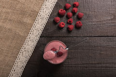 Raspberry - banana smoothie. On korichnevom the background of natural wood, lace Stock Photo