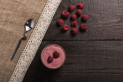 Raspberry - banana smoothie. On korichnevom the background of natural wood, lace Royalty Free Stock Photos